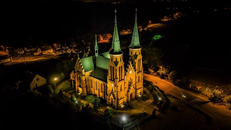 Kościół w Janowcu Kościelnym - zdjęcie nocą z lotu ptaka, kościół podświetlony.